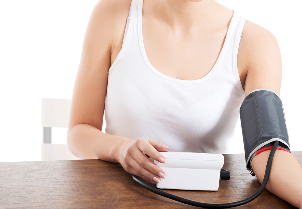 Woman in white tank top sitting at table, checking her blood pressure with the cuff around one arm and a hand on the monitor